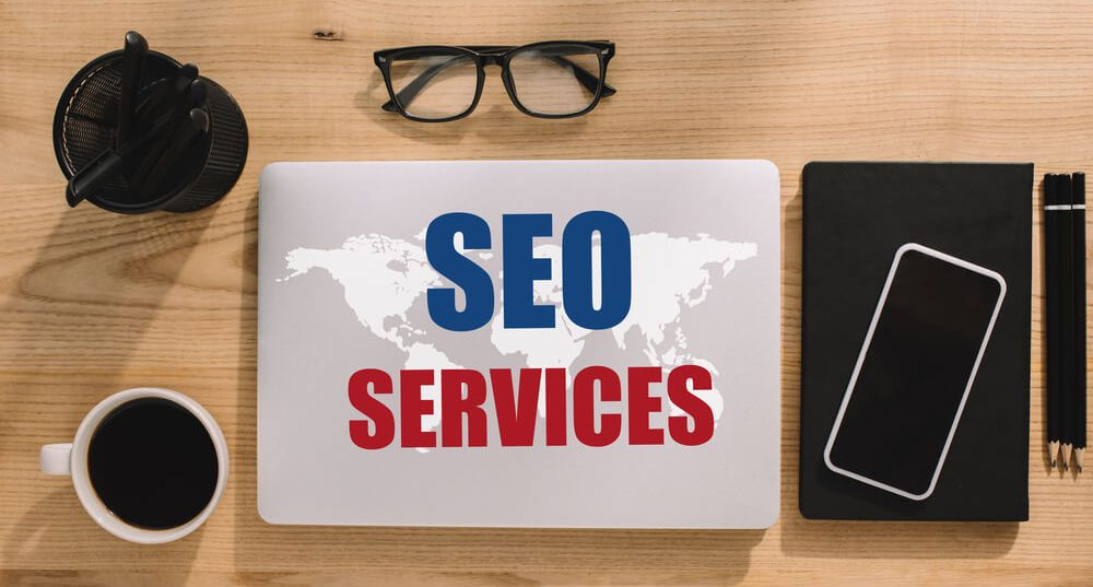 top view seo services with office gadgets - infintech designs